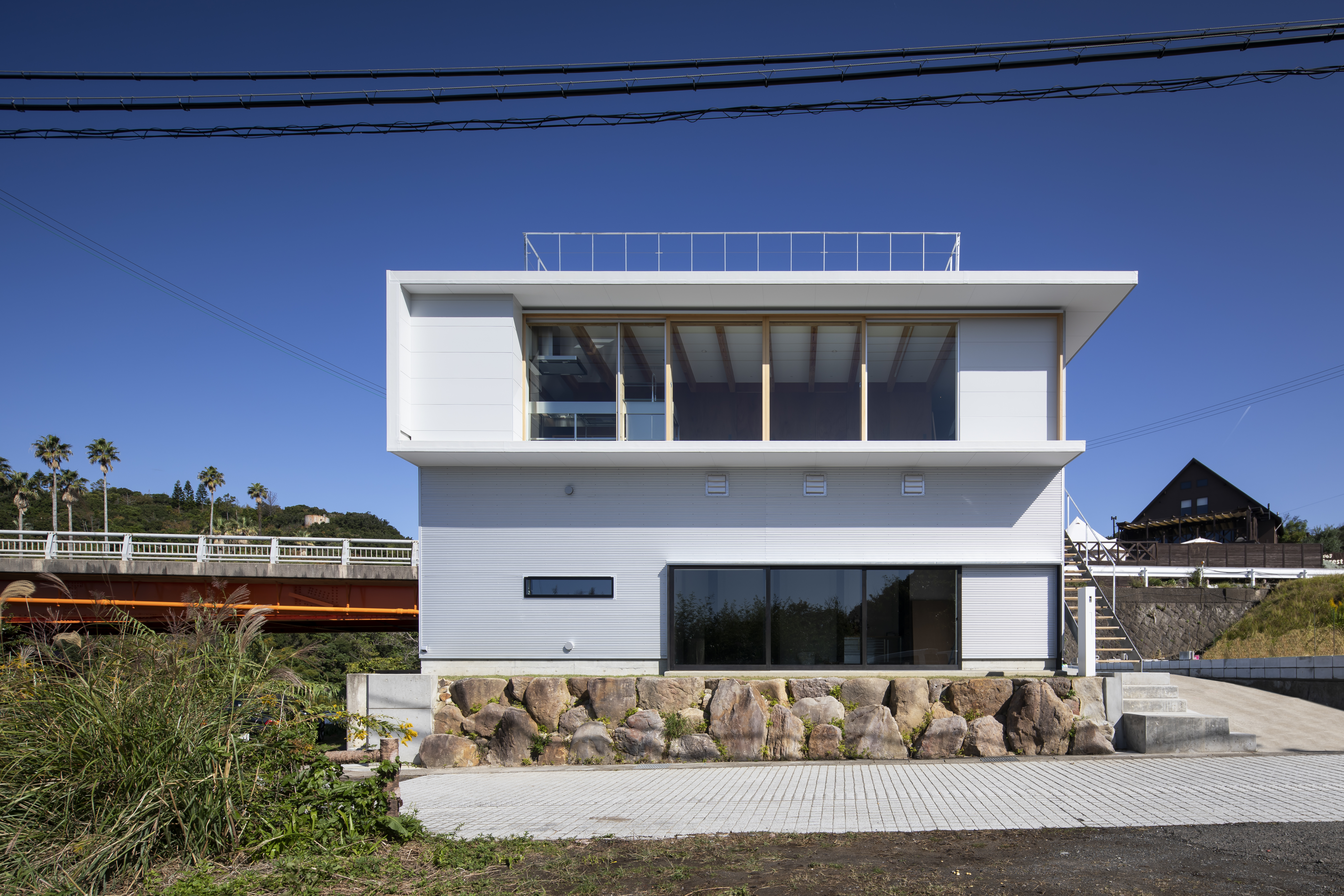 Front Facade with industrial material (1F: Galvalume corrugated sheet 2F: Fiber cement siding)