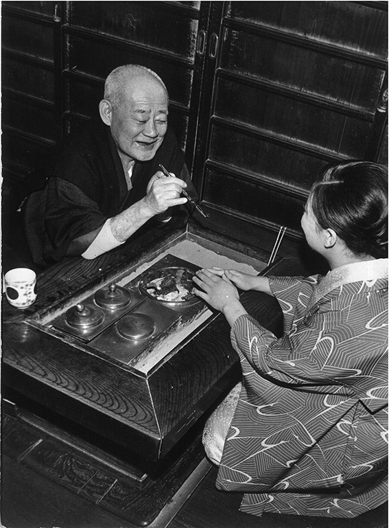 Around 1975_The owner of _Mangyokuro_geisha house is chatting with a geisha at the reception desk
