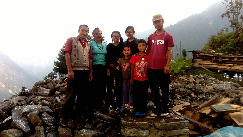 Shanti (middle back) standing at the former home where she experienced the earthquake.