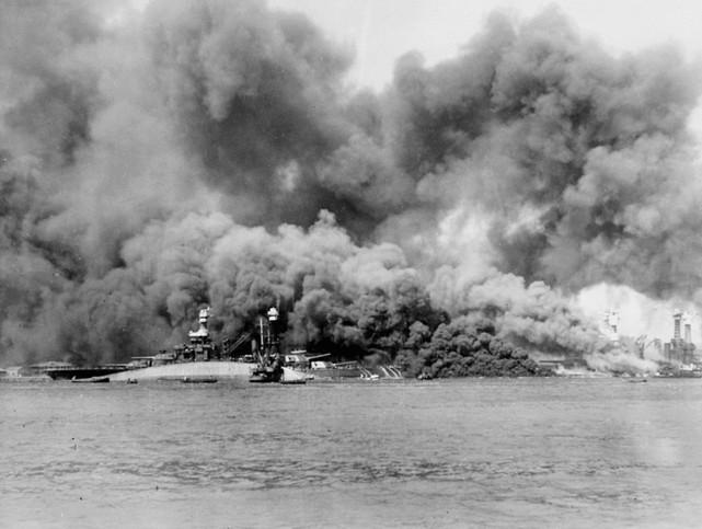 Capsized U.S.S. Oklahoma with USS Maryland in background.