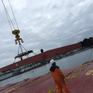 Repaired boom moved to ship's side by barge