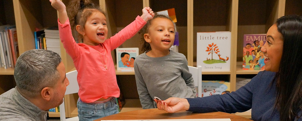 A NYC family plays with ParentCorps' Fun with Feelings play mat, which helps children name and navigate their feelings.