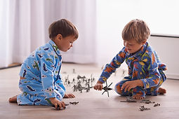 Child in dinosaur pajamas playing with toy soldiers and planes.