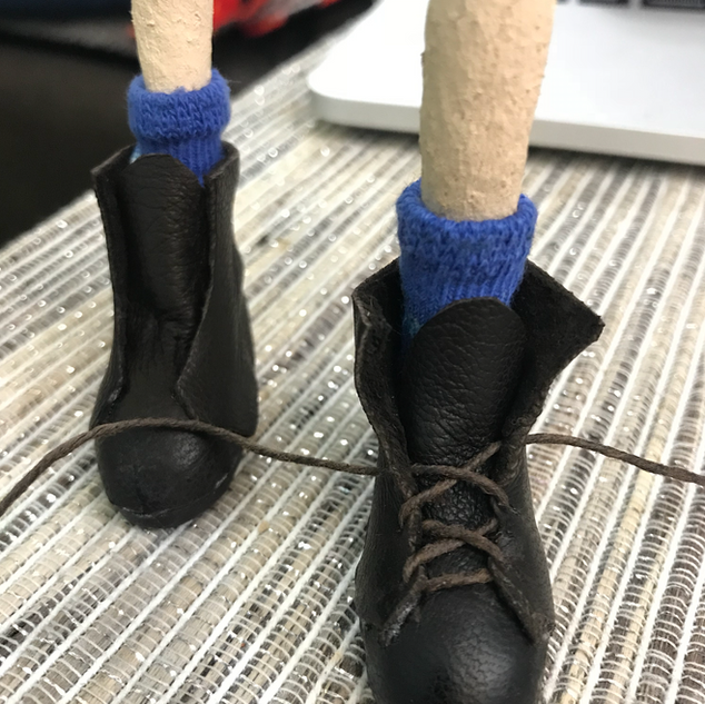 I made her boots from real leather, and punched holes so the laces could actually be tied.