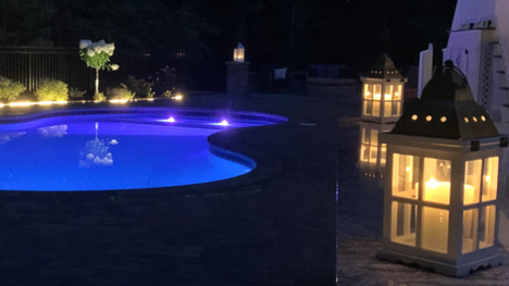 in-ground pool illuminated by blue and white lights