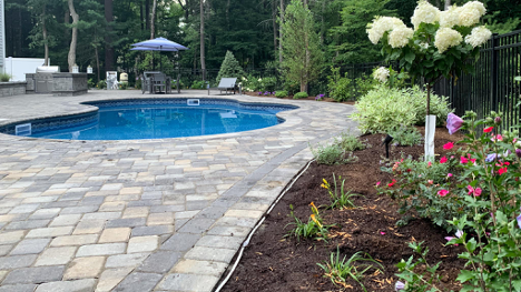 in-ground pool and patio pavers surrounded by flowers and trees