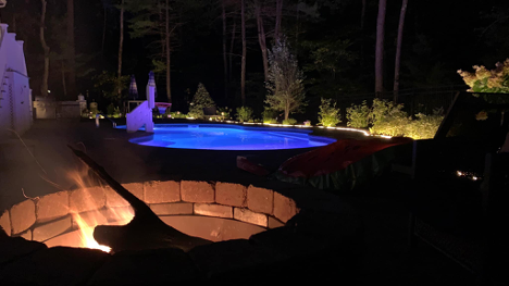 view of a fire pit and in-ground pool with lighting