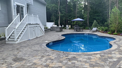 in-ground pool and patio pavers next to white stairs