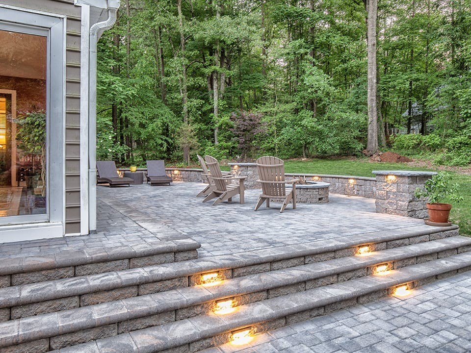Backyard patio pavers with fire pit and lighting on patio steps