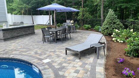 Patio furniture next to a backyard in-ground pool