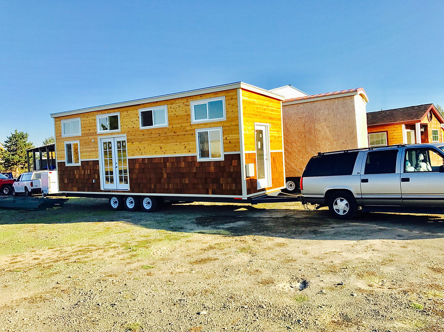 A tiny house on a trailer is being pulled by a suburban