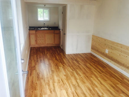 Living room layout - pecanwood laminate floor, shiplap walls, with kitchen counter in the background