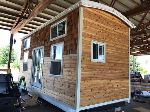 Brown shingle and tongue-and-groove cedar tiny home with white trim