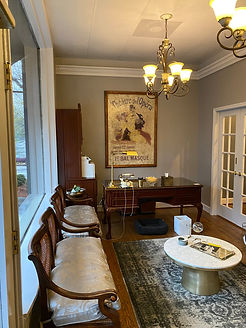 The Amy Murphy Studio's Lobby! Featuring two plush benches, a center table, two chandeliers, an oak desk, and an oriental rug.  This is where you wait for your lesson, and then enter through the french doors on your right.