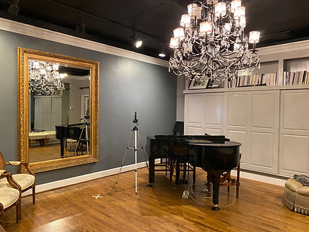 A picture of the Amy Murphy Studio! Featuring a grand piano, a bookcase spanning the entire side wall, hard wood floors, and an enormous mirror. There is also filming equipment if a singer needs to self tape