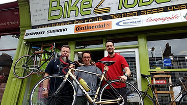 Bikeztube's workshop staff and mechanics holding a Schwinn bicycle after a full repair service and custom build