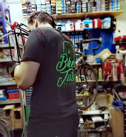 Bicycle mechanic servicing bike on stand for full repair Specialized bicycle racer