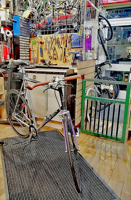 Raleigh fixie single speed bicycle inside bike workshop to be fixed and tools