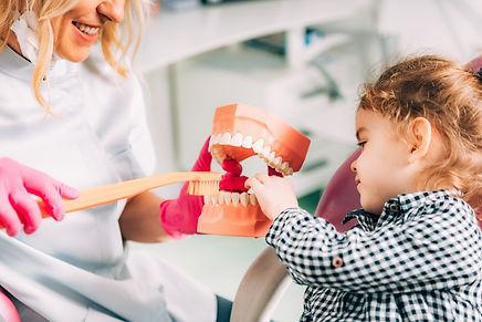 little-girl-at-dental-clinic-learning-how-to-brush-H4PDSKJ.jpg