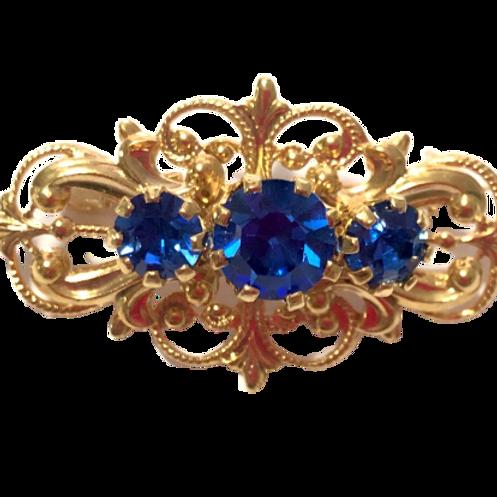 Broche dourado com strass azul royal