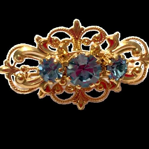 Broche dourado com strass azul