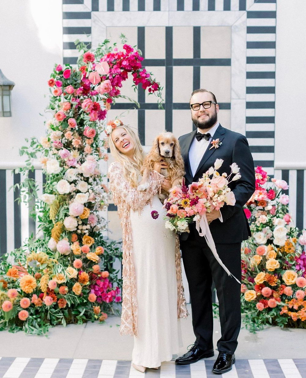 A newly-wed couple holding their dog while stood in front of a flower arch