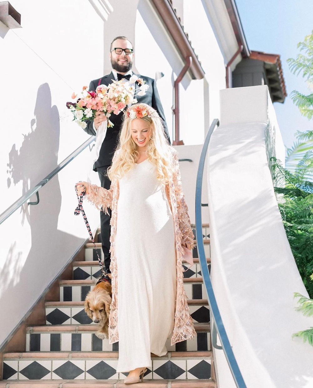 A newlywed couple walking down the stairs with their dog