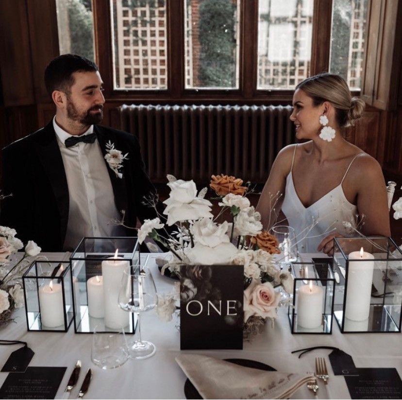 Man and woman sat at a wedding table smiling at each other
