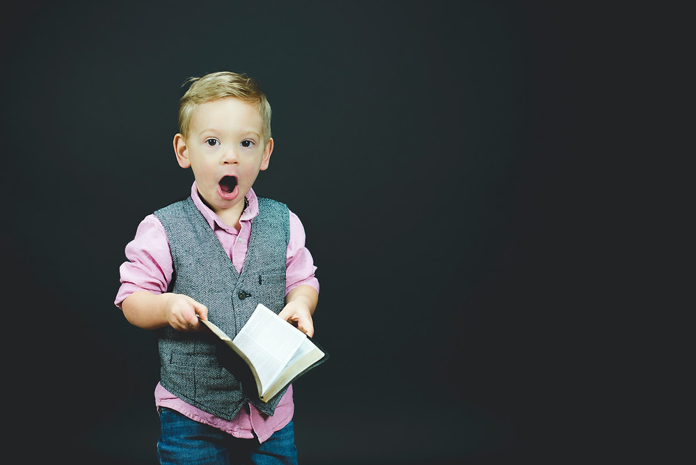 Young boy wearing a waistcoat holding an open book