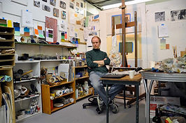 A teaching artists conducts a painting demonstration of a live model in a classroom