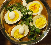 Simon Majumdar's Life Saving Dahl with lentils topped with halved hard boiled eggs, drops of yogurt and cilantro leaves