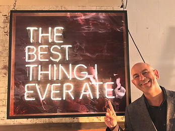 "Simon Majumdar in front of sign, ""Best Thing I Ever Ate."""