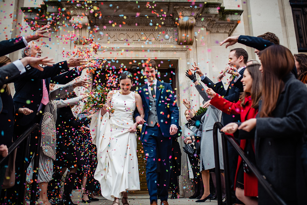 Newlywed couple leaving wedding with guests throwing confetti