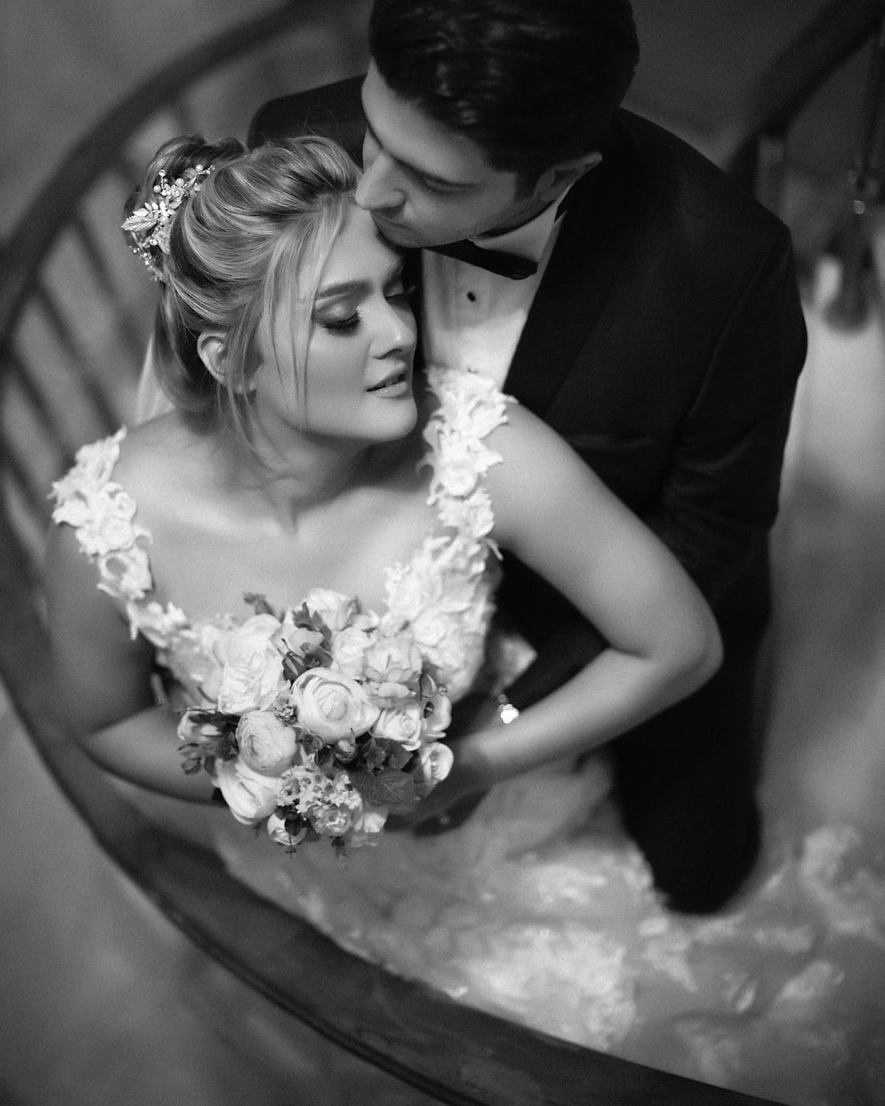Newlyweds posing for a photo on a spiral staircase
