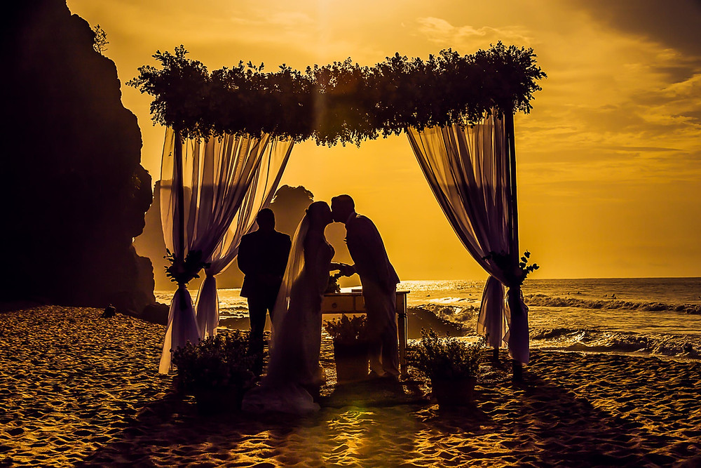 Micro wedding couple kissing under a canopy on a beach in the sunset