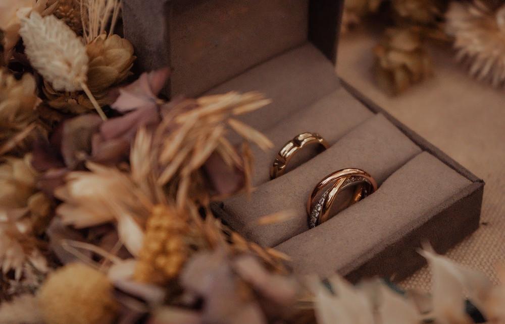 Wedding rings nestled in amongst autumnal leaves