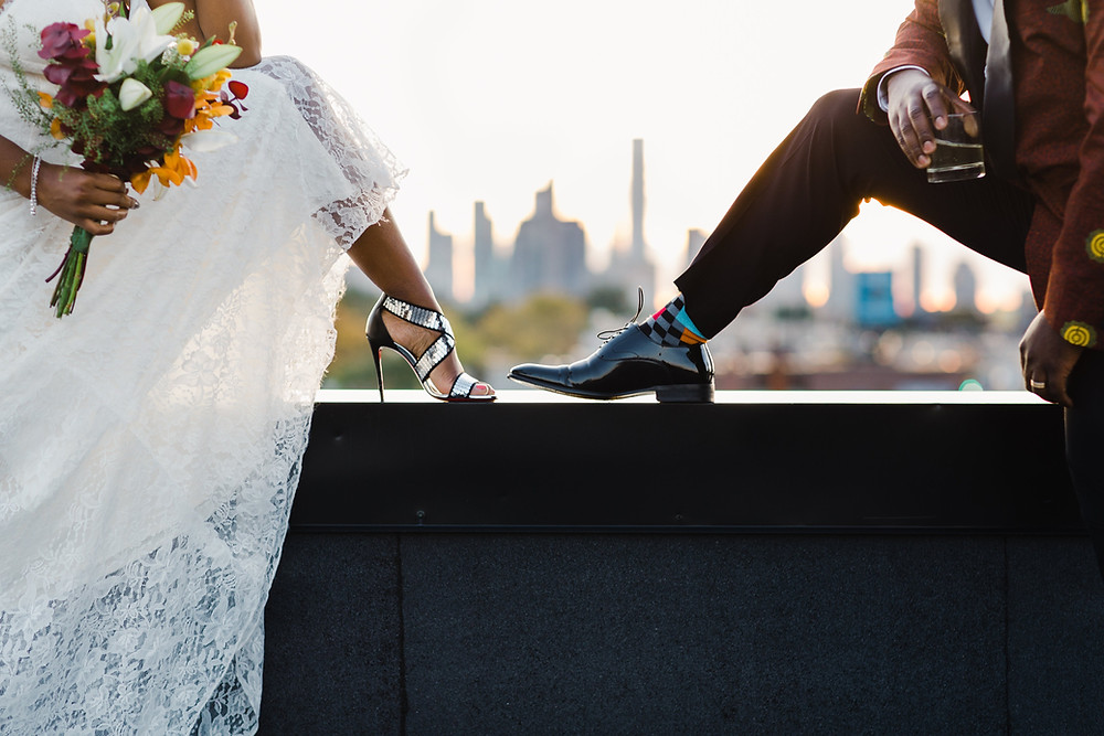 Bride and groom with feet up on wall overlooking city