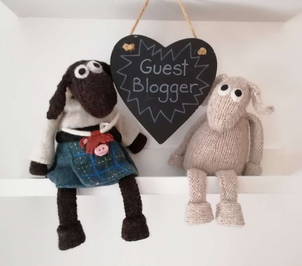 "Ramsay MacSporran and Dolly (Wee Blackface Sheep Toys designed by Janice Anderson) shown in front of a heart-shape chalkboard that reads ""Guest Blogger"""