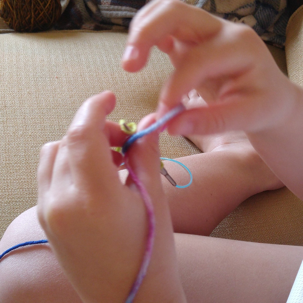 Hands of Little Miss trying to master the slipped knot