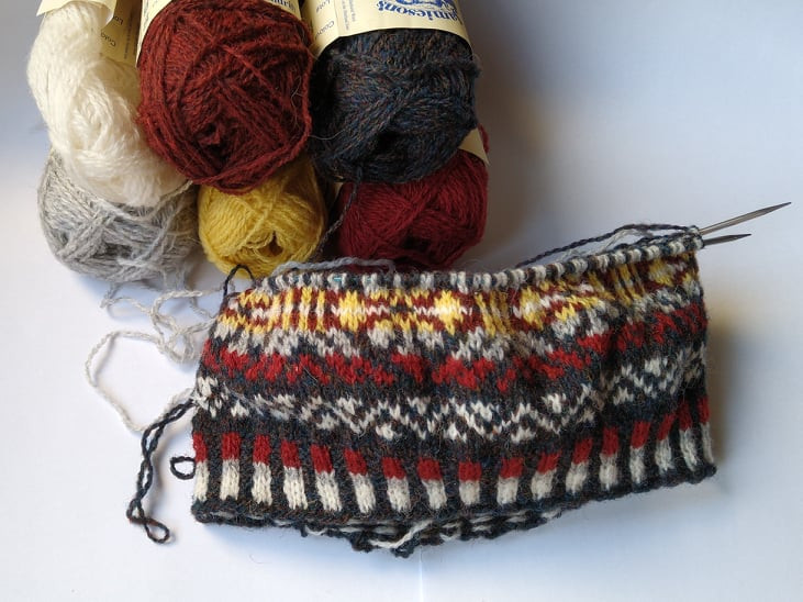 Da Crofter's Kep on the needles, work in progress, in shades of red, brown, grey, white and yellow.