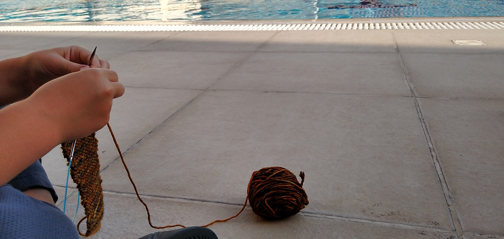 Hands of little boy, knitting by a pool. Ball of yar rolling on the ground