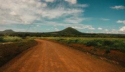photo-of-dirt-road-across-hill-under-clo