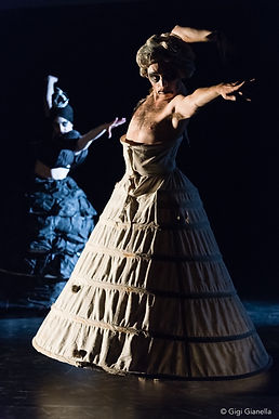 Two dancers, in huge bell shaped dresses, one in a white dress and one in black in a black dress both stood in the same position. Their left arm reaches straight out beyond their shoulders with their graze reaching beyond their left hand. Their right arm is bent sharply behind their heads.