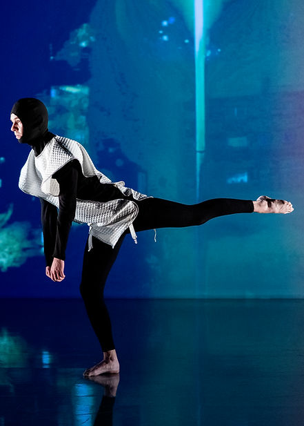 A dancer stands on one leg in a scene of blue kaleidoscopic light. One of his legs is stretched out directly behind them with their body leant forward.