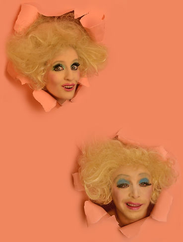 Two heads protrude from torn pink paper. They have the same big blond hair and dishevelled looking makeup. One looks manically happy and the other smiles with crossed eyes.
