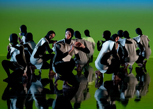 Many figures kneeling near to the floor with their backs straight and hands near to their ears as though listening. They are on a mirrored floor against a grass green backdrop.