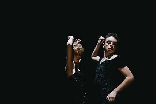 Two people in black dresses dancing together. They look as though they are dancing in a club as they are sweaty and unabashed. The lighting is strong, creating interesting shadows and they are against a jet black background.
