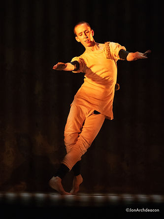 A dancer in an orange light wearing light coloured top and trousers with black bands around elbows and ankles is mid moving. They are leaning out to their side as if being blown about in the wind.