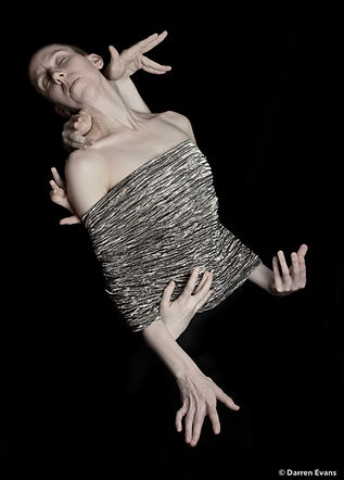 Just the head and torso of a single dancer is seen within a backdrop of black. Their torso from below the shoulders in draped in a crumpled silver material. There are six hands surrounding them and seemingly coming out of them. There eyes are closed as if sleeping.
