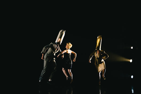 A woman in a black dress dancing around two figures in a suit and dress suit who both have crown that are so large they cover their entire heads. There are stage lights hitting them from the side.